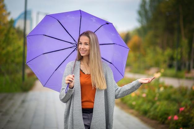Portret dziewczyna z purpurowym parasolem w jesień parku