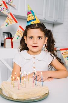 Portret dziewczyna z urodzinowym tortem na kolorowych świeczkach