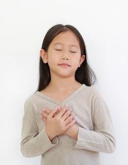 Portret dziewczynki azjatyckie zamknięte oczy i trzymając się za ręce na geście serca miłości. dziecko umieścić ramiona na klatce piersiowej na białym tle.