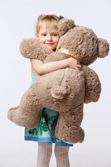 Portret dziewczynki blondynka przytulanie pluszowego misia