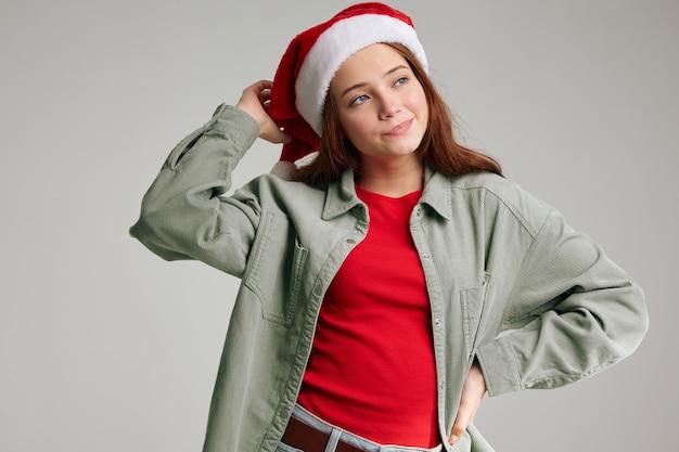 Portret dziewczynki czerwone czapki z pomponem na szarym tle przycięty widok na boże narodzenie nowy rok. wysokiej jakości zdjęcie