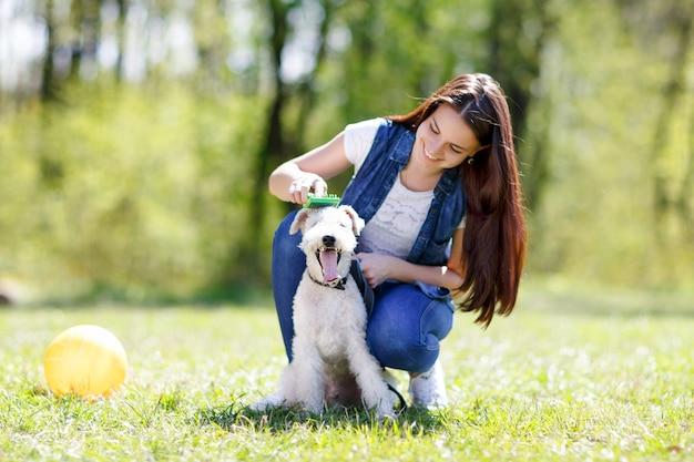 Portret dziewczynki czesanie psa na świeżym powietrzu w parku