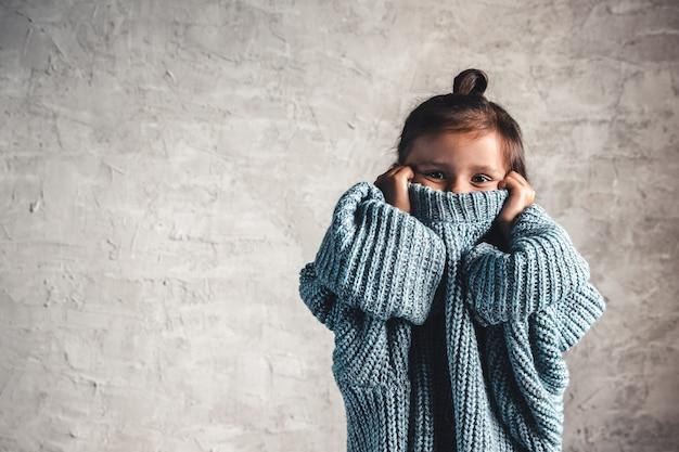 Portret dziewczynki dzieciak moda na szarej ścianie