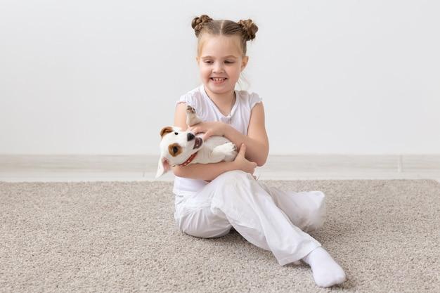 Portret dziewczynki dziecko siedzi na podłodze z szczeniakiem