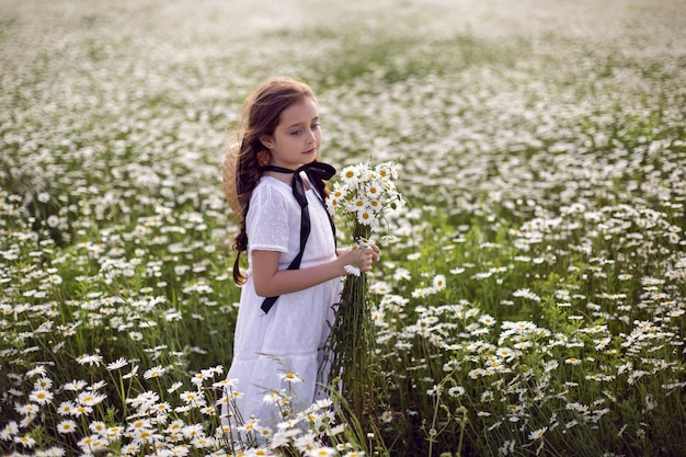 Portret dziewczynki dziecko w białej sukni stoi na polu rumianku w kapeluszu iz bukietem kwiatów