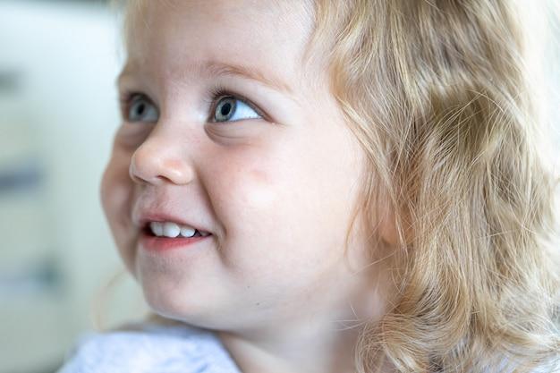Portret dziewczynki, dziewczyna patrzy w bok i uśmiecha się.