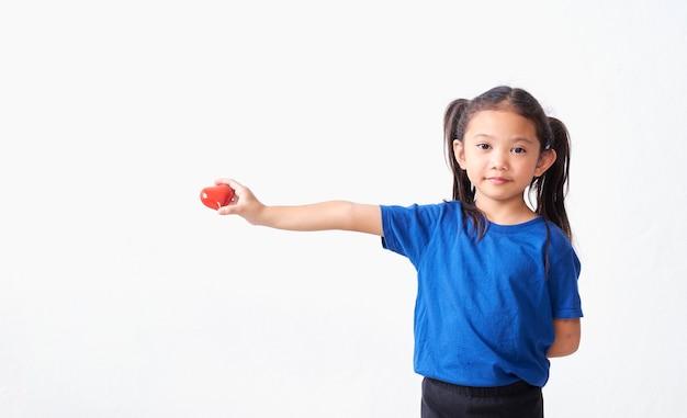 Portret dziewczynki gospodarstwa czerwone serce na białym tle.