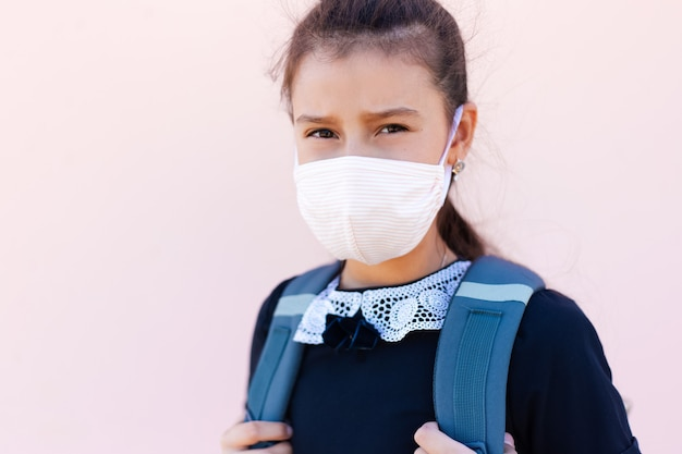 Portret dziewczynki gotowej do szkoły, noszącej medyczną maskę przeciw koronawirusowi lub covid-19 w pastelowym różowym kolorze.