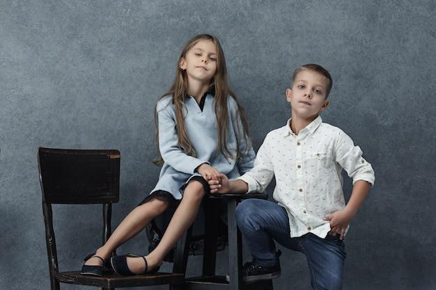 Portret dziewczynki i chłopca na szarej ścianie