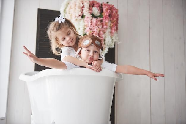 Portret dziewczynki i chłopca w kapeluszu pilota, grając w łazience u pilotów lub żeglarzy. podróż, dzieciństwo i realizacja marzeń