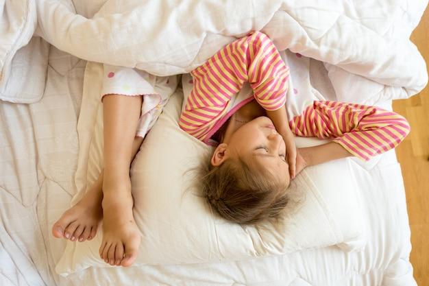 Portret dziewczynki i siostry stóp na poduszce w łóżku