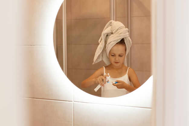 Portret dziewczynki, która myje zęby w wannie, stojąc przed lustrem, owinięta białym ręcznikiem, wyciskając pastę do zębów z tubki, poranna rutyna.