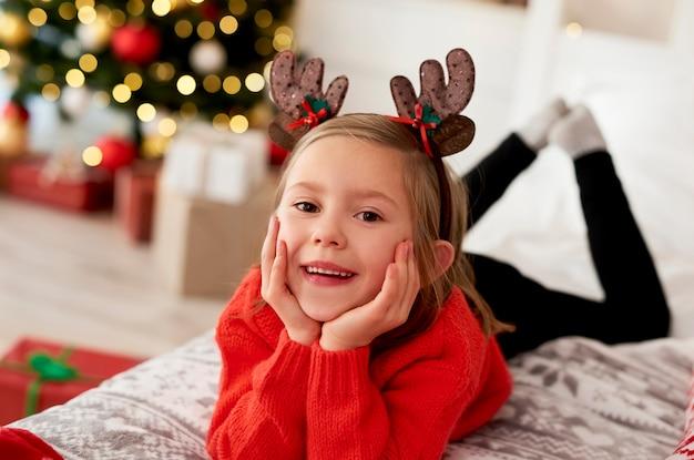Portret dziewczynki leżącej na łóżku w stroju bożonarodzeniowym