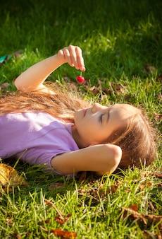 Portret dziewczynki leżącej na trawie i patrzącej na czerwoną wiśnię