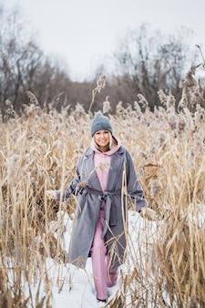Portret dziewczynki o europejskim wyglądzie na zimowym spacerze, trawa, las, pole, kapelusz, zdrowie