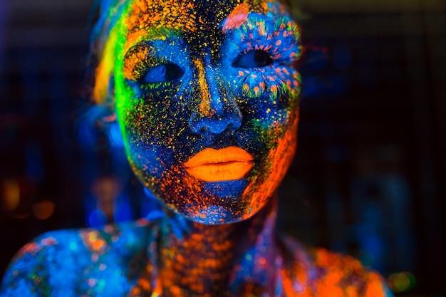Portret dziewczynki pomalowanej proszkiem fluorescencyjnym.