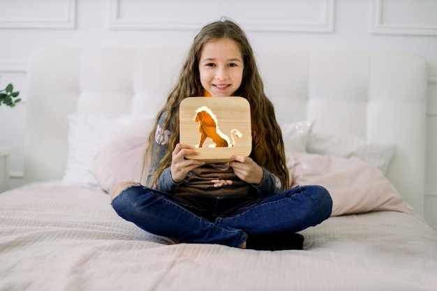 Portret dziewczynki siedzącej na łóżku w pozycji lotosu i trzymającej stylową drewnianą lampkę nocną z obrazkiem niedźwiedzia.