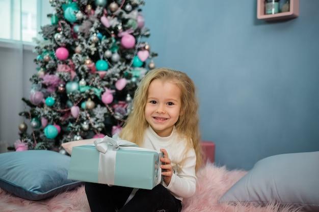 Portret dziewczynki siedzącej na łóżku z prezentem na boże narodzenie