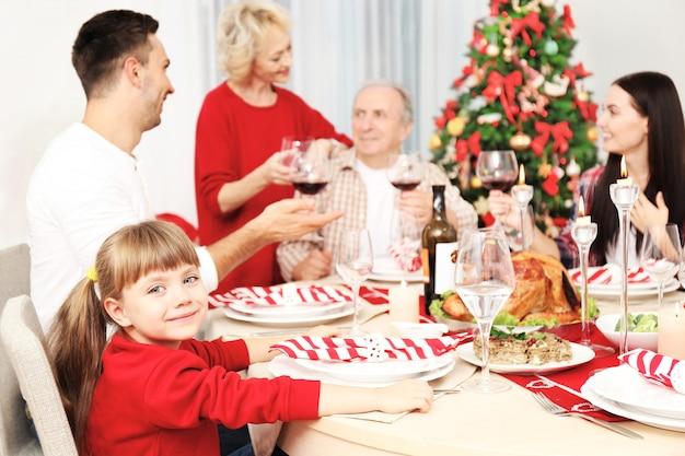 Portret dziewczynki siedzącej przy stole z rodziną podczas świątecznej kolacji
