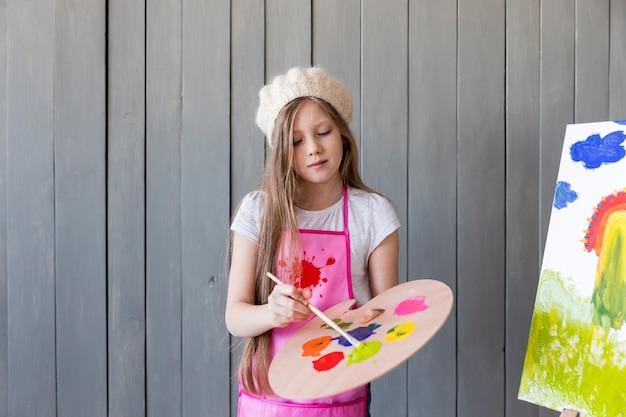 Portret dziewczynki stojącej przed szary obraz ścienny pędzlem przeciwko szarej ścianie