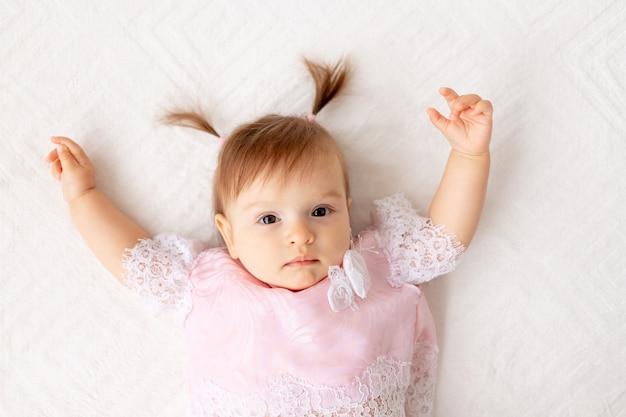 Portret dziewczynki sześć miesięcy na białym łóżku w różowe ubrania z rękami do góry