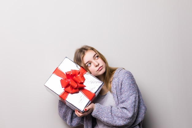 Portret dziewczynki teen gospodarstwa teraźniejszości i słuchania wewnątrz pudełka na białym tle