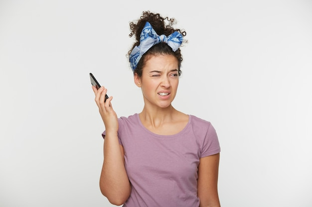 Portret dziewczynki trzyma telefon w pewnej odległości od głowy