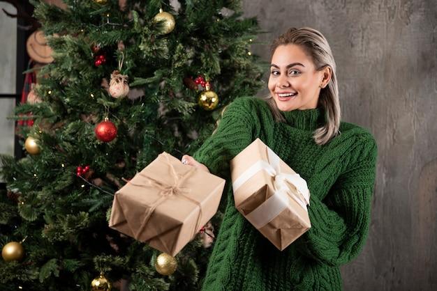 Portret dziewczynki ubrany w zielony sweter dając prezent pod choinkę