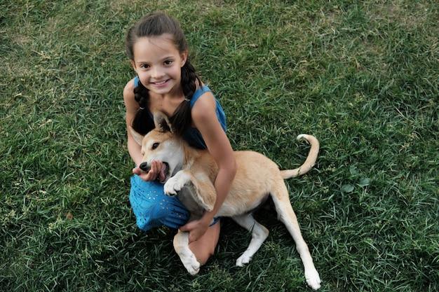Portret dziewczynki uśmiecha się siedząc na trawie i bawiąc się z psem na zewnątrz