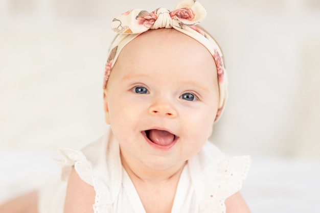 Portret dziewczynki uśmiechniętej lub śmiejącej się leżącej na białym bawełnianym łóżku w domu