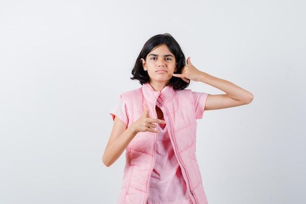 Portret dziewczynki w białej koszulce i kamizelce puffer pokazując gest telefonu