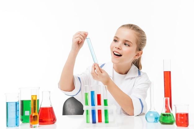 Portret dziewczynki w białym fartuchu laboratoryjnym, który przeprowadza eksperymenty chemiczne z wielobarwną cieczą w probówkach izolowanych na białej ścianie