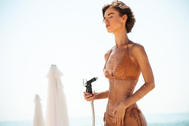 Portret dziewczynki w bikini za pomocą węża na plaży. młoda dama w beżowym stroju kąpielowym spłukuje piasek ze swojego ciała na plaży. ładna dziewczyna marzycielsko zamykając oczy podczas wylewania wody z węża na plaży