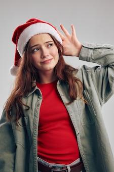 Portret dziewczynki w czapeczkach na szarym tle gestykuluje rękami