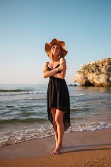 Portret dziewczynki w czarnej sukni i kapeluszu na plaży