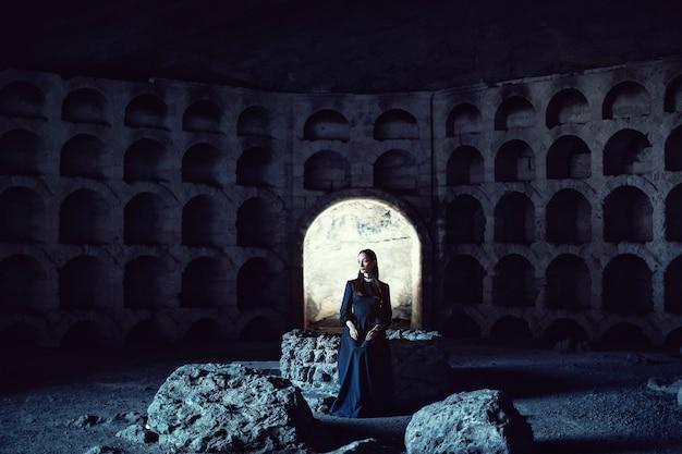 Portret dziewczynki w czarnej sukni z białym kołnierzykiem siedzącej na kamieniu oraz w kamiennym otworze
