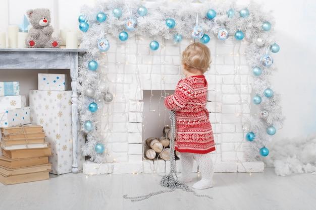 Portret dziewczynki w czerwonej sukience przy ceglanym kominku w świątecznie urządzonym domu. święta bożego narodzenia w pomieszczeniu z zabawkami i pudełkiem