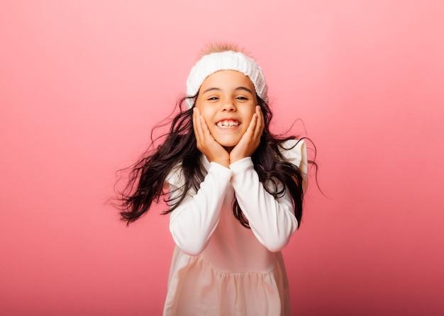 Portret dziewczynki w dzianinowej białej czapce zimowej i białej sukience na różowym tle