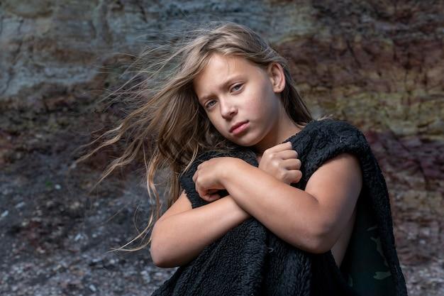 Portret dziewczynki w futrzanej kurtce bez rękawów u stóp klifu