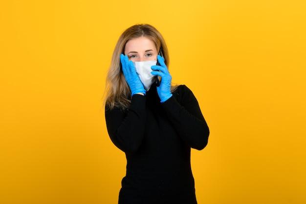 Portret dziewczynki w masce medycznej, która zakłada gumową rękawiczkę. żółto-szare tło. skopiuj miejsce.