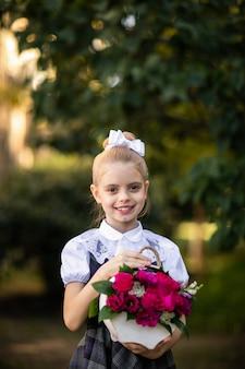 Portret dziewczynki w mundurku szkolnym, trzymając bukiet kwiatów