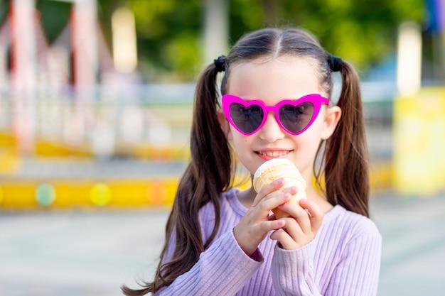 Portret dziewczynki w parku rozrywki latem jedzącej lody w pobliżu karuzeli i uśmiechającej się ze szczęścia w okularach przeciwsłonecznych, koncepcja weekendów i wakacji szkolnych