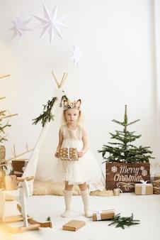 Portret dziewczynki w pobliżu wigwamu i choinki rozpakowywania prezentów na białym tle