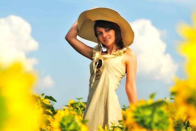 Portret dziewczynki w polu słoneczników. kobieta w letniej beżowej sukience i kapeluszu, ręka podniosła się