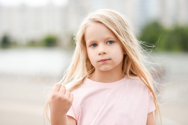 Portret dziewczynki w różowej koszuli na ulicy.