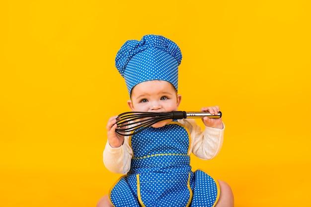 Portret dziewczynki w stroju szefa kuchni, trzymając trzepaczkę na żółtej ścianie z miejscem na tekst
