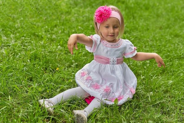 Portret dziewczynki w sukience i kokardą na głowie. dziecko siedzi na zielonej trawie z rozłożonymi rękami