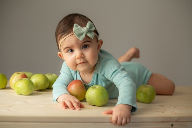 Portret dziewczynki w zielonym body na drewnianym stole ze świeżymi zielonymi jabłkami. naturalne produkty dla dzieci. zdjęcie wysokiej jakości