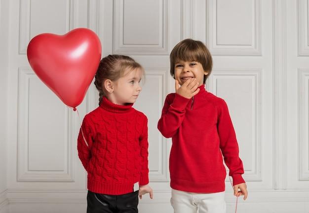Portret dziewczynki z czerwonym balonem w kształcie serca i chłopca na białym tle