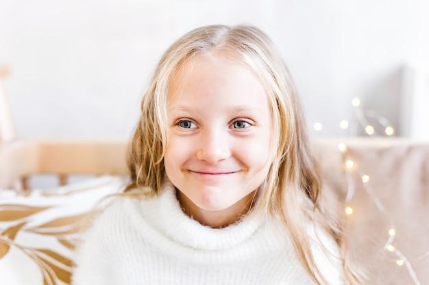 Portret dziewczynki z długimi blond włosami dom udekorowany na boże narodzenie